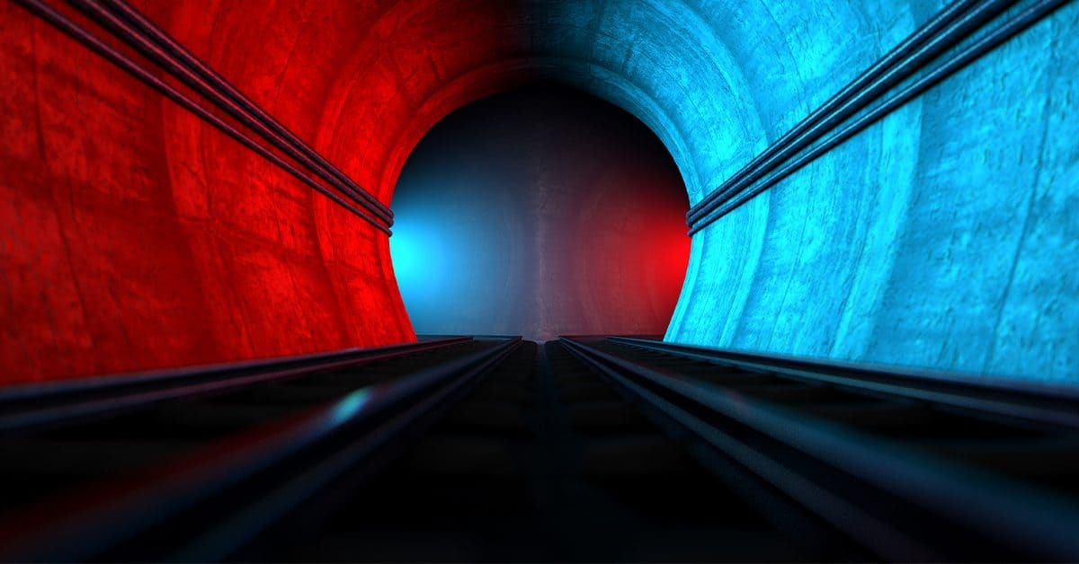 Diverging subway tunnel with red and blue lights on either side