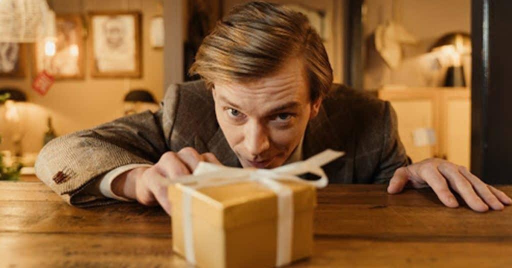 Man reaching towards small gift box.